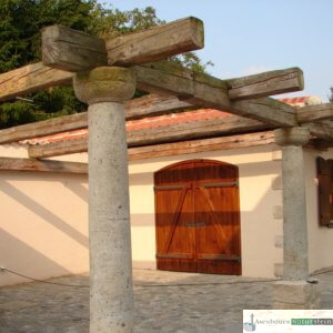antike Granitsäulen mit alten Holzbalken