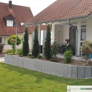 Terrasseneinfassung aus Granitleisten dunkelgrau, Rasenkante aus Betonpflster