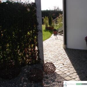 Weg mit antiken Pflastersteinen, Sichtschutz aus Granit- Pfosten und Efeu
