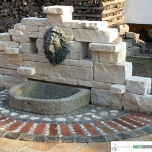 Jurakalk-Rebmauer mit Löwenkopf und antiken Brunnen