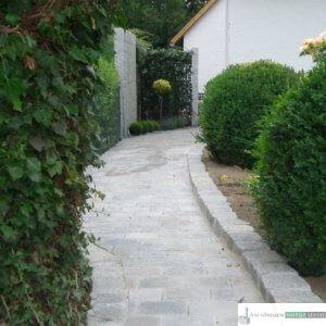 Weg aus gelblichen Betonpflaster, Einfasungen aus Granit